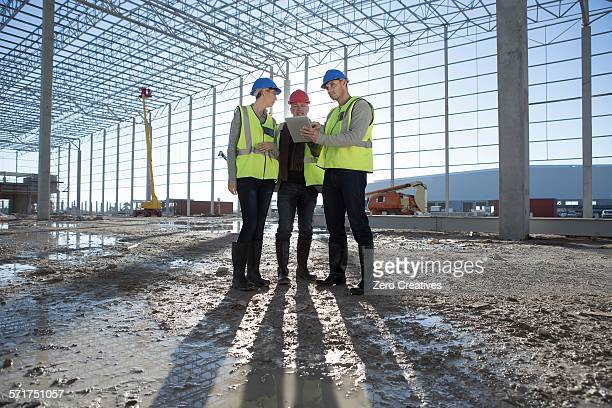 Architect and builders meeting on construction site