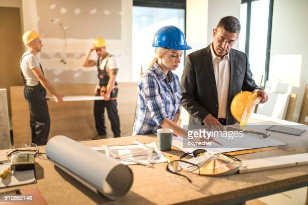 architect and building contractor going through housing plan at construction site. - instructions stock pictures, royalty-free photos & images