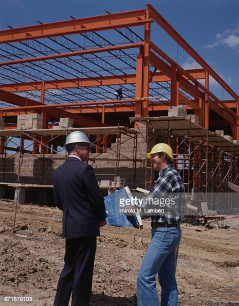 architect and construction worker discussing blue print plan at construction site - {{ contactusnotification.cta }} stockfoto's en -beelden
