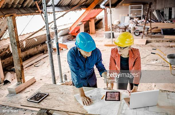 Architect And Construction Worker With Plans, Tablet PC And Laptop