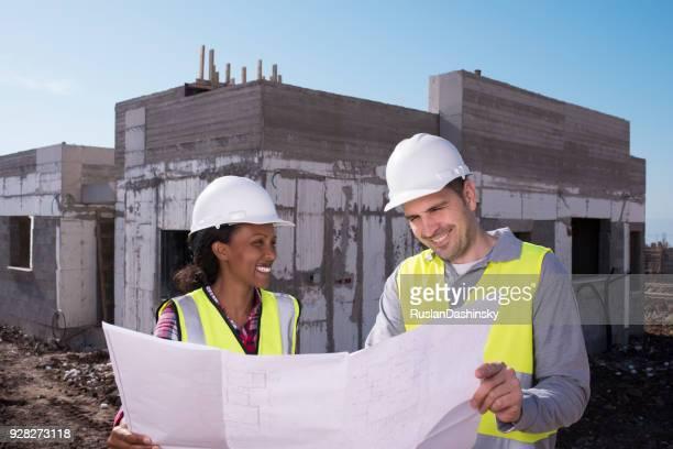 trabajador de construcción y arquitecto trabajando en el campo de la construcción. - ingeniero civil fotografías e imágenes de stock