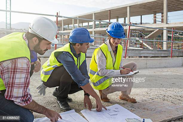 Architect and construction workers looking at blueprints on construction site