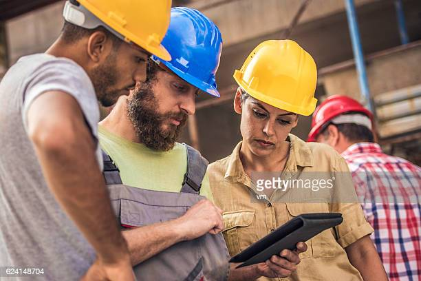 Architect and construction workers reviewing plans