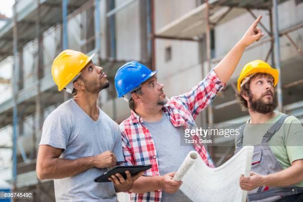 Architekten und Bauarbeiter Überprüfung Pläne zusammen