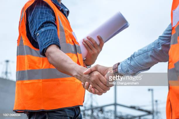 architect and construction workers shaking hands while working in the construction site - foundation make up stock pictures, royalty-free photos & images