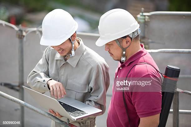 Architekt und Ingenieur schaut an digitalen Plänen in Baustelle