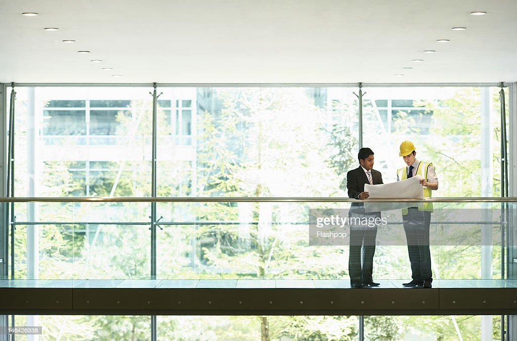 Architect and engineer looking at plans : Photo