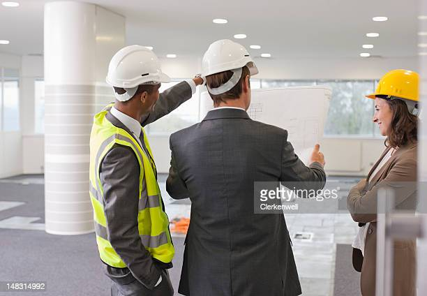Architect and engineer reviewing blueprints in empty office