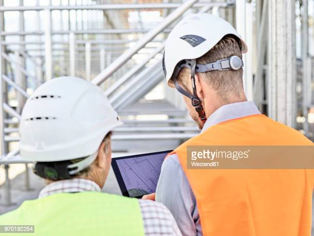 Architect and foreman with tablet wearing hards hat on construction site