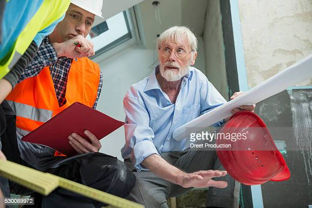 Architect and two construction workers at construction site of new building