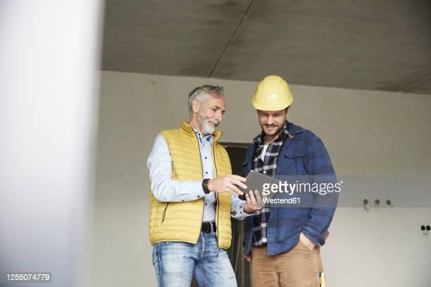 architect and worker sharing tablet on a construction site - seulement des adultes photos et images de collection