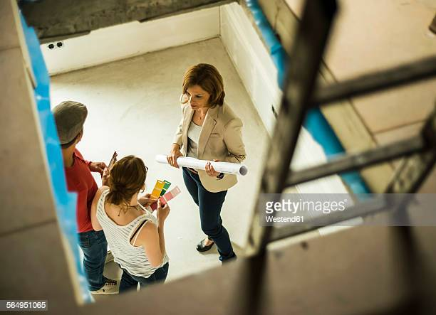 Architect and young couple discussing colour sample and construction plan