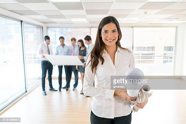 Architect at the office holding blueprints