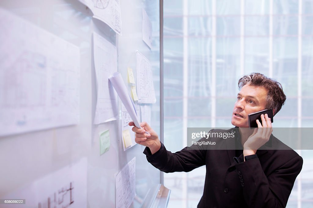 Architect designer using phone pointing to plans on wall : Stock Photo