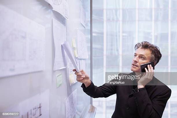 Architect designer using phone pointing to plans on wall