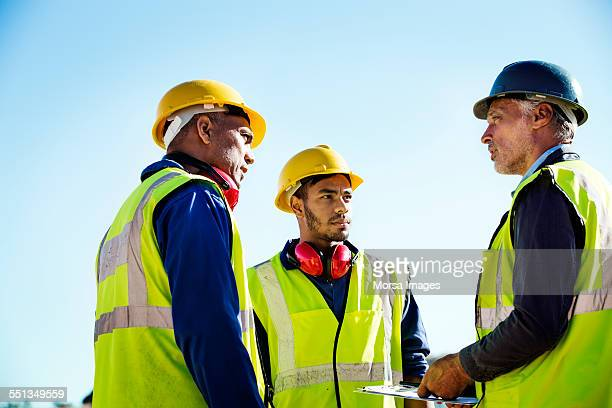 architect discussing with quarry workers - reflective clothing stock pictures, royalty-free photos & images