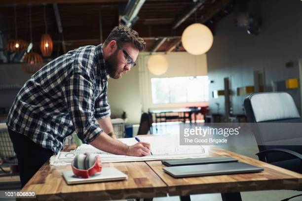 architect drafting blueprint at table in office - architect stockfoto's en -beelden
