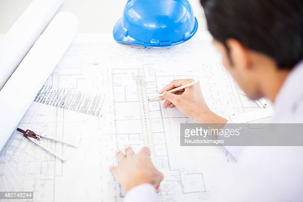 Architect Drawing On Blueprint At Desk In Office