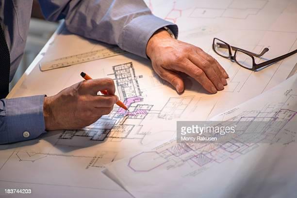 Architect drawing plans at drawing board, close up