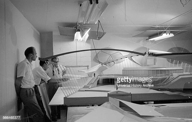 Architect Eero Saarinen 19101961 studies a scale model of the Trans World Airlines Terminal John F Kennedy Airport New York 195662