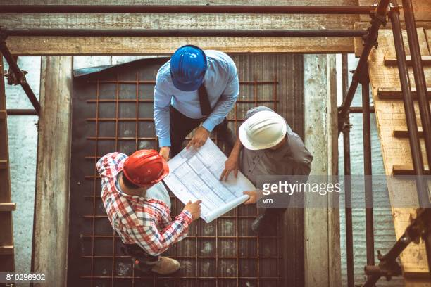 Architect, engeneer and foreman on a construction site