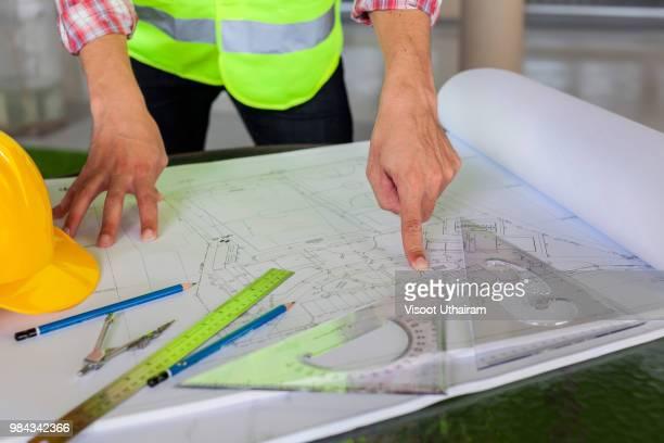 architect engineer and head constructor working on a building site holding a blueprints at construction site. - technische zeichnung stock-fotos und bilder