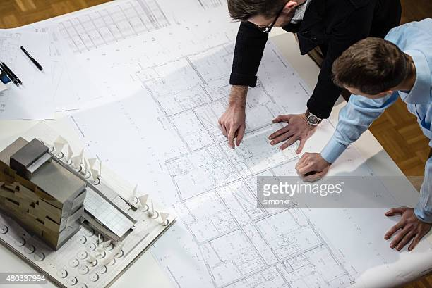 architect explaining blueprint to client - architect stockfoto's en -beelden