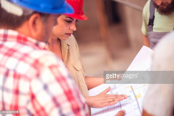 Architect explaining her plans to construction workers