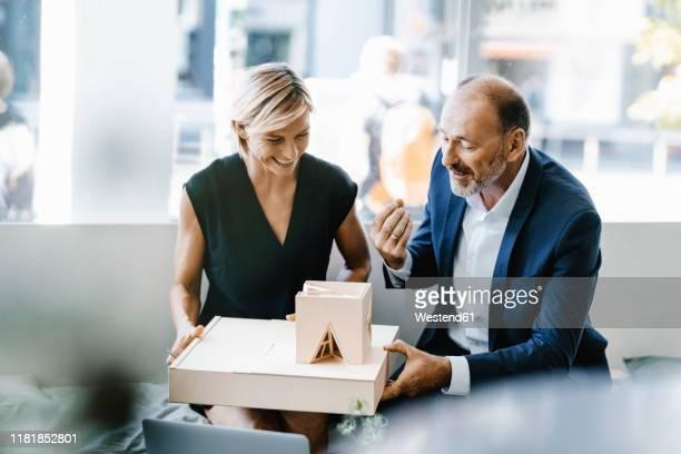 architect explaining model to customer - investition stock-fotos und bilder