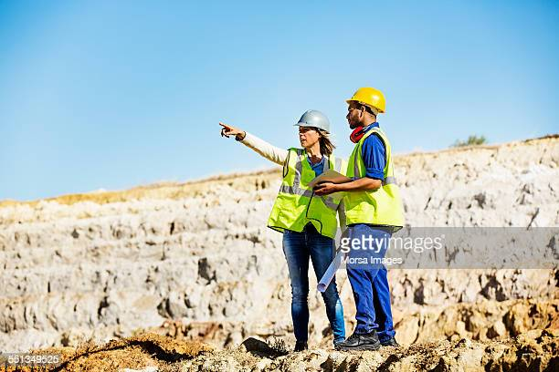 architect explaining plan to quarry worker at site - gruva bildbanksfoton och bilder