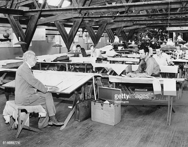 Architect Frank Lloyd Wright discusses plans with William Wesley Peters while other apprentices work at their drafting tables