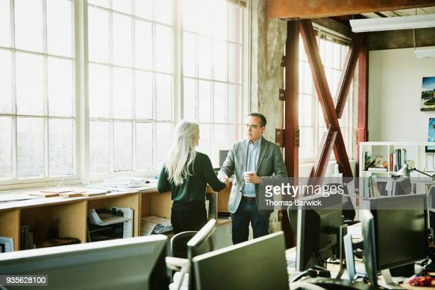 architect greeting client in office before reviewing project together - customer focused stock pictures, royalty-free photos & images