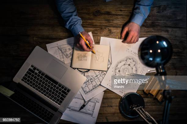 architect hand drawing at his desk - design professional stock pictures, royalty-free photos & images