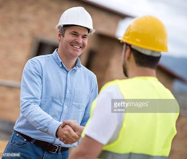Architekt handshaking ein Bauarbeiter