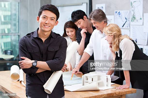 Architect holding blueprint in studio with his team in background