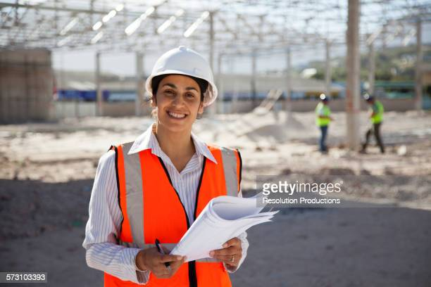 Architect holding blueprints at construction site