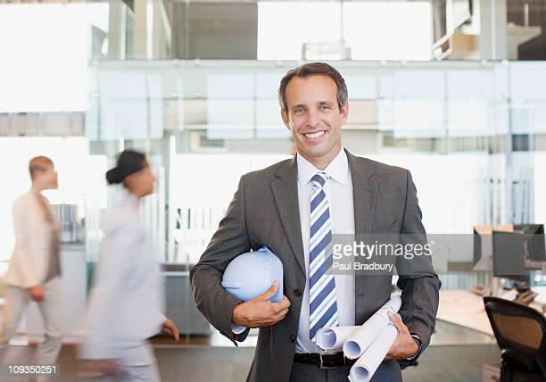 Architekt holding Werkzeuge in beschäftigt Büro