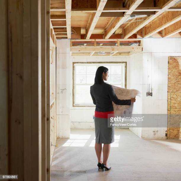 Architect holding blueprints in new home