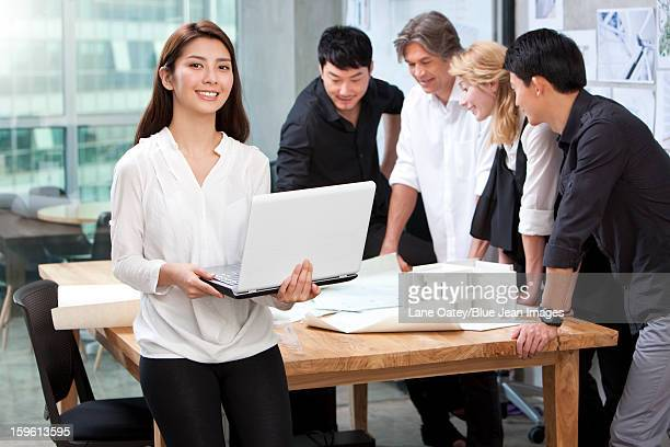 Architect holding laptop in studio with her team in background