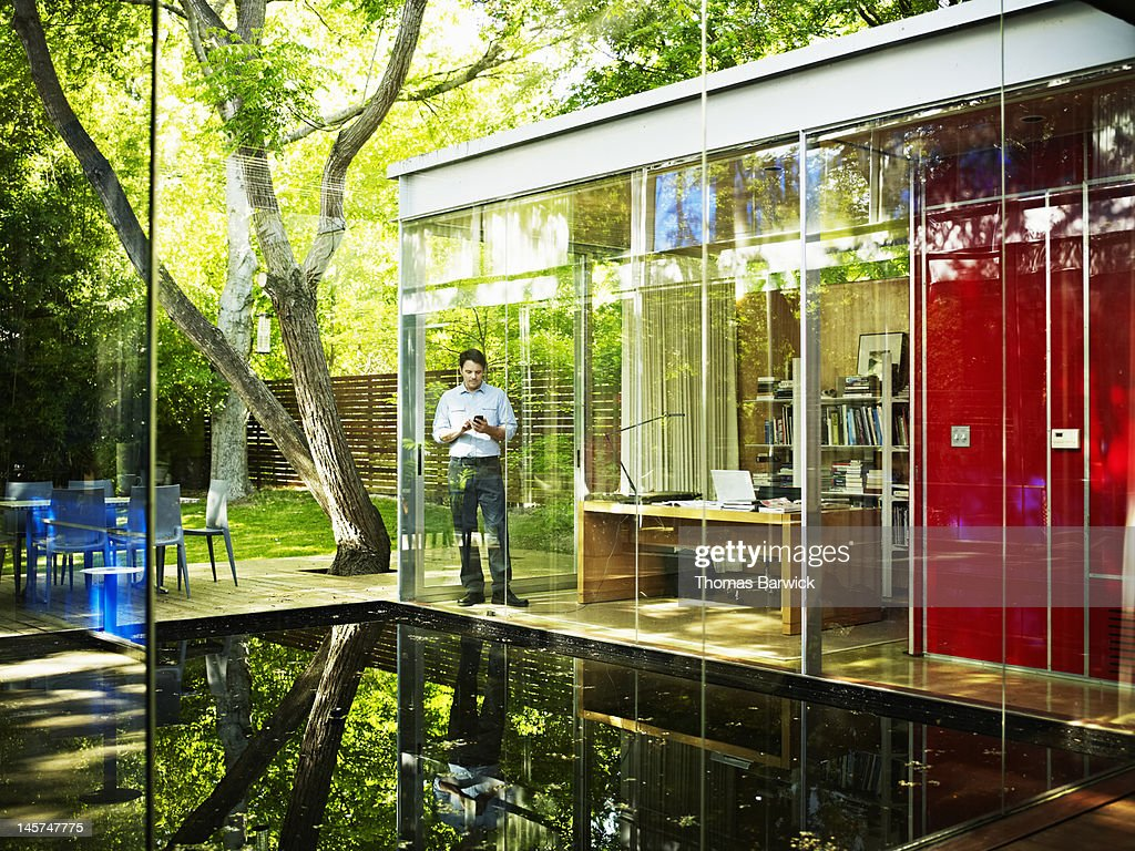 Architect in home office looking at smart phone : Stock Photo