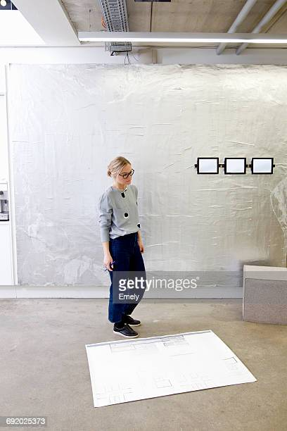 Architect in office looking at blueprint