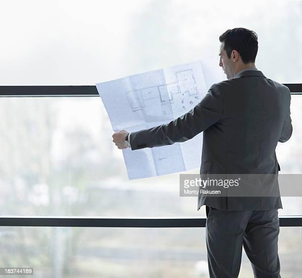 architect inspecting plans by office window - monty rakusen stock-fotos und bilder