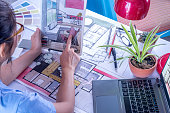 Architect, interior designer (creative) working at table in office