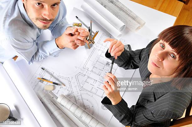 Architect is consulting with the happy client blueprints, directly above