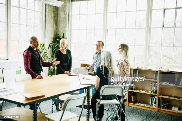 Architect leading design planning meeting at conference table in office
