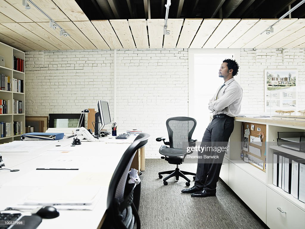 Architect leaning on bookcase in office : Stock Photo