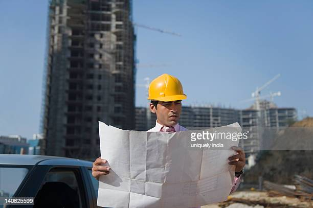Architect looking at a blueprint at a construction site, Gurgaon, Haryana, India