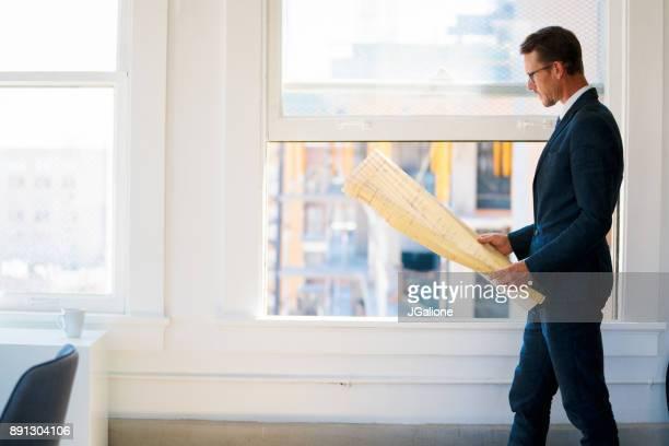 Architecte en regardant un plan dans un immeuble vide