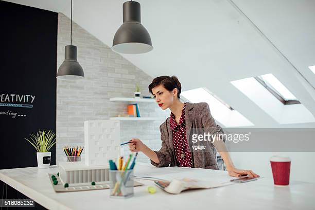 Architect Looking At Building Model In Her Office.