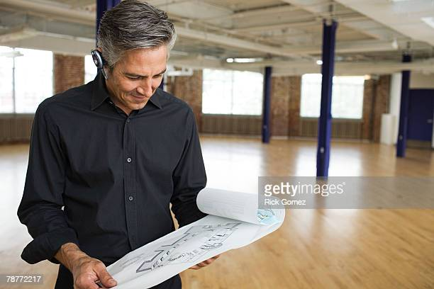 Architect Looking at Building Plans in Loft